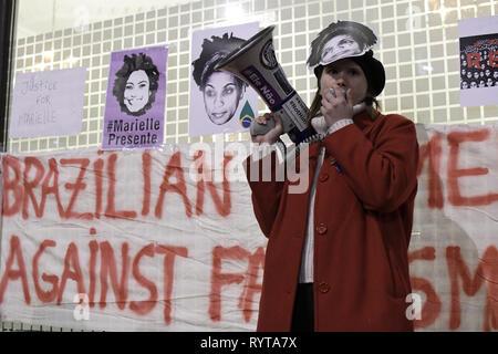 London, Greater London, UK. 14 Mär, 2019. Eine Frau beobachtet, als er sich mit den Assistenten während der Gebetswache im Speicher der Brasilianischen Aktivist Marielle Franco. Demonstranten vor der Brasilianischen Botschaft in London das Leben und das Vermächtnis des Brasilianischen Aktivist Marielle Franco, war ein ausgesprochener Kritiker der Polizeibrutalität und außergerichtliche Tötungen gegen Favela Bewohnerinnen zu Ehren versammelt. Franco wurde ermordet wegen ihrer politischen Aktivitäten zusammen mit ihrem Fahrer Anderson Gomes am 14. März in Rio de Janeiro, Brasilien 2018. Während der gebetswache Redner sprachen die Assistenten und behauptete Ju - Stockfoto