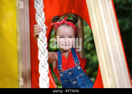 Kleines Mädchen lächelt. Kind im roten T-Shirt und Jeans auf dem Spielplatz spielt. - Stockfoto