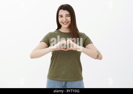 Taille - geschossen von Art und aufrichtigen attraktive junge Brünette mit Tattoo zeigen Herz Schild über Körper und lächelte süß an der Kamera als bekennende in Liebe - Stockfoto
