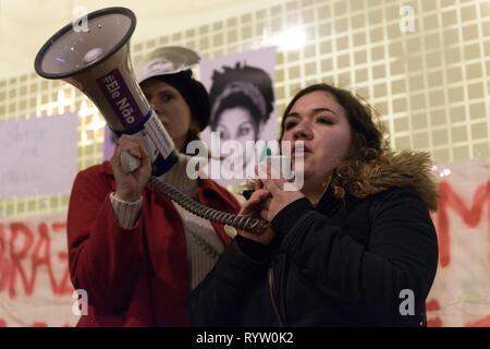 Eine Frau beobachtet, als er sich mit den Assistenten während der Gebetswache im Speicher der Brasilianischen Aktivist Marielle Franco. Die Demonstranten versammelten sich vor der Brasilianischen Botschaft in London das Leben und das Vermächtnis des Brasilianischen Aktivist Marielle Franco, war ein ausgesprochener Kritiker der Polizeibrutalität und außergerichtliche Tötungen gegen Favela Bewohnerinnen zu ehren. Franco wurde ermordet wegen ihrer politischen Aktivitäten zusammen mit ihrem Fahrer Anderson Gomes am 14. März in Rio de Janeiro, Brasilien 2018. Während der gebetswache Redner sprachen die Assistenten und beanspruchten Gerechtigkeit und forderten das Ende der Straflosigkeit in Francos cri - Stockfoto