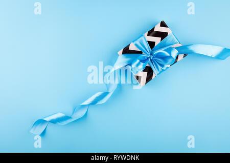 Geschenkbox aus schwarzem und weißem Papier mit blauer Schleife auf einem blauen Hintergrund, Kopieren, Vater tag Karte gewickelt, urlaub Konzept - Stockfoto