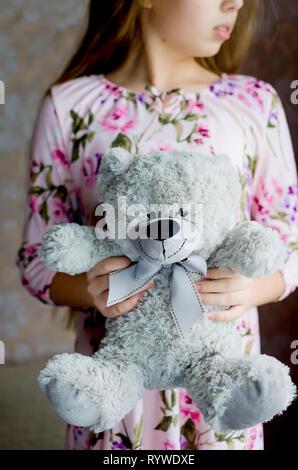 Jugendlicher Mädchen mit blonden langen Haaren in ein rosa Kleid mit einem Teddy graue Bär Tageslicht selektiven Fokus - Stockfoto