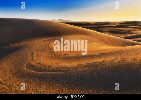 Sonne beleuchteten Oberfläche von Sanddünen bei Sonnenaufgang mit unberührten Landschaft und Fläche der Wüste an der Pazifikküste von Australien in Stockton Strand. - Stockfoto