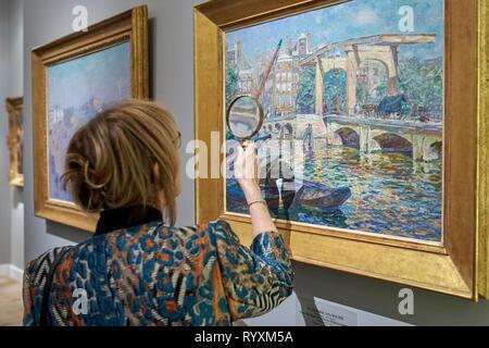 Ein Besucher der Messe stellt mit einer Lupe die Angaben zu einem der ausgestellten Bilder. Die TEFAF (The European Fine Art Fair), einer der berühmtesten Kunst-, Antiquitäten- und Messen der Welt, ist auch in diesem Jahr wieder statt. Jedes Jahr, Maastricht hosts ein Ereignis, das zusammen bringt 275 Galerien rund 20 Länder, über 30.000 ausgestellte Kunst Objekte und hat mehr als 75.000 Teilnehmer pro Jahr. - Stockfoto