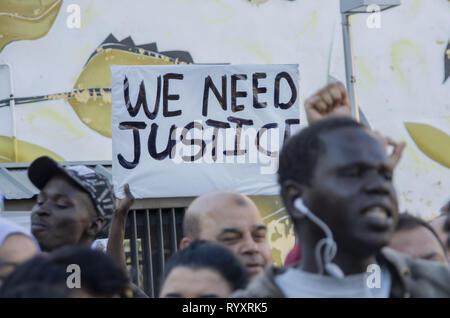 Madrid, Madrid, Spanien. 15 Mär, 2019. Eine Plakette, die sagt, 'Wir brauchen Gerechtigkeit'' Während des Protestes gesehen. Protest gegen institutionellen Rassismus fand am Nelson Mandela Square in Madrid ein Jahr nach dem Tod von Mame Mbaye, einem senegalesischen Straßenverkäufer, starb, während er von der Polizei für den Verkauf auf der Straße gejagt werden. Nach Angaben der Demonstranten, der junge Mann hatte keine legalen Papiere trotz mehr als 10 Jahre in Spanien verbracht und Behörden hat seine Familie nicht nach seinem Tod. Sie bezahlten auch Hommage an die Opfer des New Zeland Terroranschlag in Moscheen. (Credi - Stockfoto