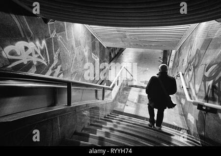 Die Silhouette des Mannes, absteigend ist die Treppe in der Stadt U-Bahn, nachts in der Stadt, die Schwarz-Weiß-Fotografie - Stockfoto