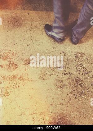 Beine und Füße eines Mannes in Schwarz Schuhe und casual Lshirt stehend auf einem Zementuntergrund mit nassen Fußspuren - Stockfoto