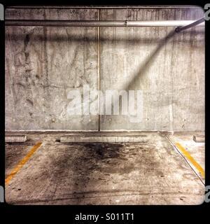 Einem einzigen Schatten auf einer Wand in einem düsteren Parkhaus mit Ölflecken auf dem Boden.