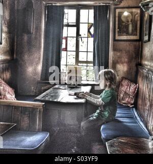 Junge sitzt auf seinem eigenen an einem Tisch in einem alten pub - Stockfoto