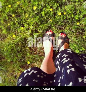 Blickte auf Füße in Sandalen und ein Sommerkleid, stehend auf einem LAN mit kleinen gelben Blüten - Stockfoto