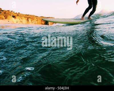Surfer auf einem Longboard bei Sonnenuntergang im Sommer - Stockfoto