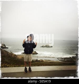 Sechs Jahre alter Junge lustige Grimassen am Rande einer Klippe. Lands End, Sutro Bezirk San Francisco, Kalifornien, - Stockfoto
