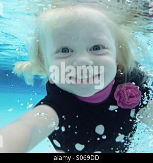 Junges Mädchen lächelnd als She schwimmt in Richtung Kamera unter Wasser. - Stockfoto