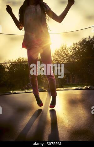 Bounce. Ein junges Mädchen, das Hüpfen auf einem Garten Trampolin - Spaß - Stockfoto