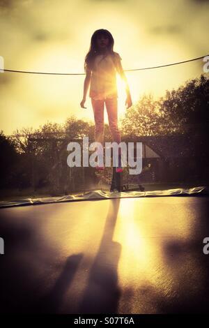 Starten. Ein junges Mädchen, das Hüpfen auf einem Garten Trampolin - Lift off-Alltag ungerade - Stockfoto