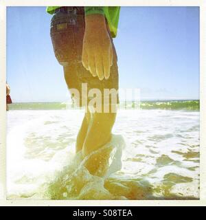 Ein sechs Jahre alter Junge steht in der Brandung Seabright State Beach. Santa Cruz, Kalifornien, USA