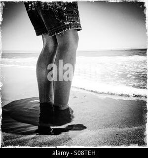 Ein sechs Jahre alter Junge steht im Sand und Surfen Seabright State Beach. Santa Cruz, Kalifornien, USA
