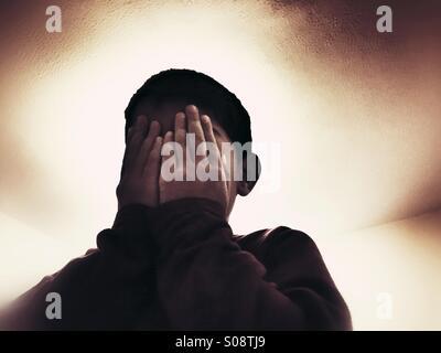 Angst vor jungen Gesicht in Händen versteckt - Stockfoto