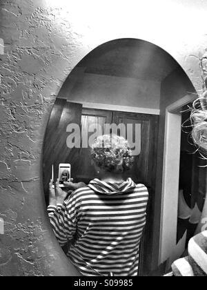 Eine ältere Frau kaukasischen nimmt ein Handy-Foto von der Rückseite der Haare mit einem Spiegel. - Stockfoto
