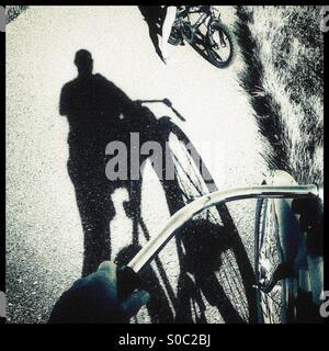 Ein Schatten ein Radfahrer auf einem Radweg im Gespräch mit einem Kind mit dem Fahrrad. - Stockfoto