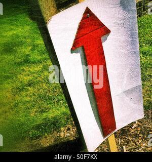 Ein roter Pfeil auf einem Schild am Straßenrand weist den Weg zu gehen. - Stockfoto