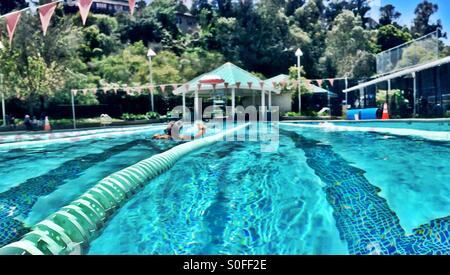 Frau mit Kickboard in Outdoor-olympisches Schwimmbad 25 m treten. San Francisco Bay Area, Kalifornien, USA. - Stockfoto