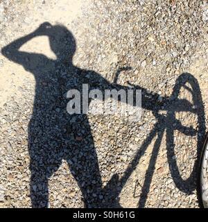 Schatten eines Menschen Trinkwasser stand neben einem Mountainbike in der Toskana, Italien. - Stockfoto