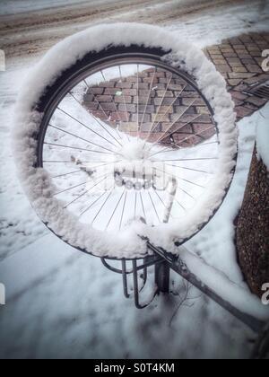 Ein Rad von einem gestohlenen Fahrrad links auf einem Fahrrad Parken Rack schneebedeckt, Berlin, Deutschland - Stockfoto
