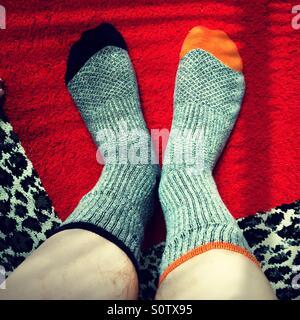 Mann nicht übereinstimmenden grauen Socken mit blauen und orangefarbenen Zehen auf einem Leopard und roten quadratischen - Stockfoto