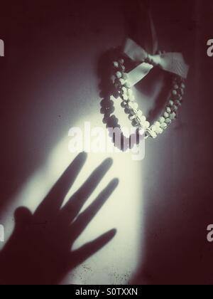 Dekorative Girlande Gießen Schatten in Herzform mit gruseligen Schatten Hand greift dafür - Stockfoto