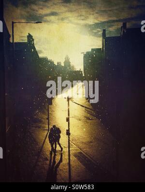 Paare, die bei Sonnenuntergang in einer leeren Stadt. - Stockfoto