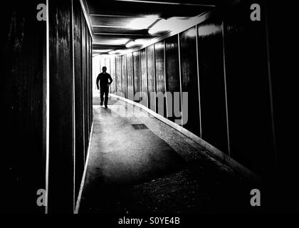 Bin Mann Schwellenländern in einen dunklen geheimnisvollen tunnel - Stockfoto