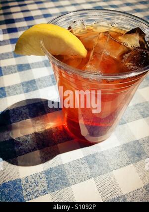 Eistee mit Zitronenscheibe im Plastikbecher auf blauen und weißen aufgegebenes Tischdecke serviert. - Stockfoto