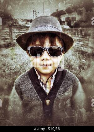 Ein Junge trägt einen Hut und eine Sonnenbrille. - Stockfoto