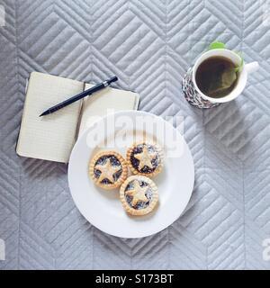 Mince Pies auf einem Teller, Kräutertee und ein Notizbuch mit Bleistift - Stockfoto