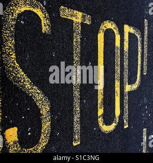 Gelb lackierte Straße Kennzeichnung Zeichen auf schwarzem Asphalt mit dem Wort Stop. - Stockfoto