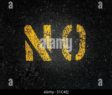 Gelb lackierte Straße Kennzeichnung Zeichen auf schwarzem Asphalt Darstellung das Wort Nein. - Stockfoto