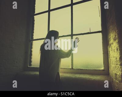 Hintere Ansicht Silhouette einer jungen Frau, Blick aus dem Fenster Hand berühren des Glases - Stockfoto