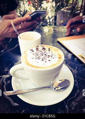 Tasse Cappuccino Kaffee während der anstrengenden Arbeitszeit - Stockfoto