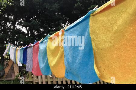 Eine Wäscheleine voll von fröhlich farbigen Tücher trocknen in der Sonne. - Stockfoto