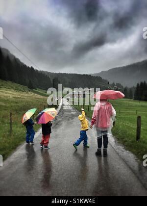 Kinder und eine Frau in Regenbekleidung auf einer Straße auf dem Lande - Stockfoto