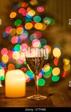 Festliche Wein Glas mit bunten Holiday Lights aus dem Weihnachtsbaum erstellen bokeh Hintergrund - Stockfoto