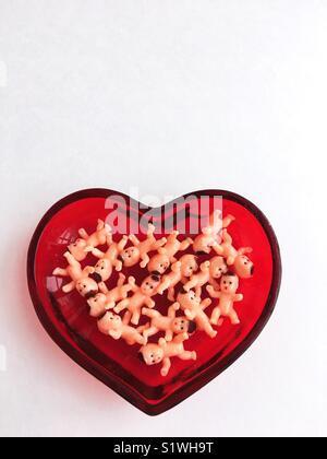 Kunststoff Spielzeug baby Puppen in Herzform Teller. - Stockfoto