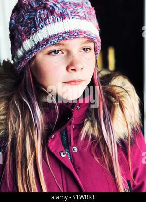Porträt der 10 Jahre alte Mädchen mit lila Haaren streifen tragen Winter Mantel und Hut stricken an der Seite suchen - Stockfoto
