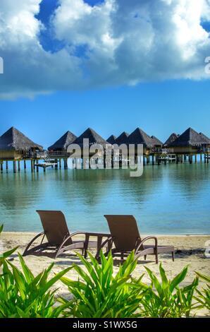 Liegestühle am Strand auf Bora Bora, Französisch-polynesien im Südpazifik. Über das Wasser bungalows durch die Flitterwochen - Stockfoto