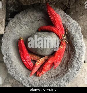 Red Hot Chili Peppers in Stein Mörser Pistill bereit, als Zutat in der Küche vorbereitet werden. Auf Rote Chilis in Stein Mörser Pistill. - Stockfoto