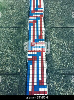 Die roten, weißen und blauen Mosaikfliesen auf einem Bürgersteig in Seattle. - Stockfoto