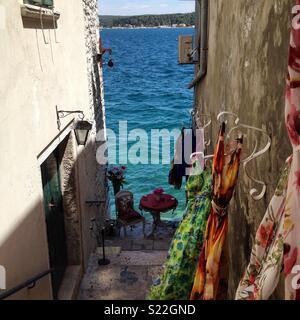 Schönen gepflasterten Seitenstraße, sieht hinunter zum Meer, in die kroatische Stadt Rovinj entfernt. Die schöne bunte Tücher wehen sanft im Wind in der sonst leere Straße. - Stockfoto