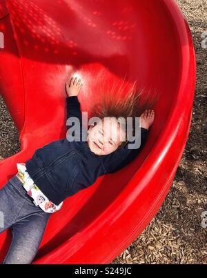 Aktion Bild von Toddler girl herunter rutscht, rote Folie mit Armen und Haaren bis klemmt - Stockfoto
