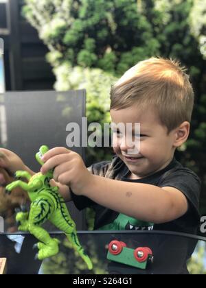 Ein Junge spielt mit seinem Spielzeug Dinosaurier - Stockfoto